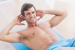 Smiling shirtless young man doing sit ups in fitness studio Stock Photo