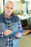 Smiling shoemaker holding clipboard and spectacle in workshop. Senior royalty free stock photo