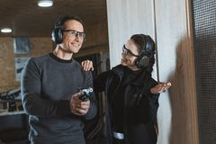 Smiling shooting instructor supporting client. In shooting gallery stock photography