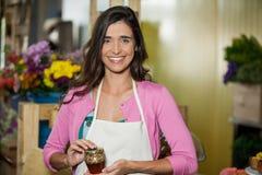 Smiling shop assistant holding a jar of pickle Stock Images