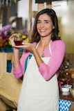 Smiling shop assistant holding a jar of pickle Stock Photography