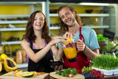 Smiling shop assistant preparing juice at health grocery shop Stock Images