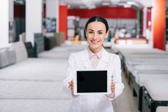 smiling shop assistant in white coat showing tablet with blank screen in furniture shop stock photography