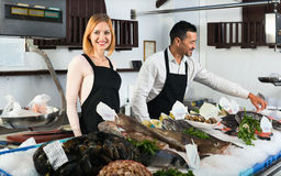 Smiling shop assistants selling fresh fish Royalty Free Stock Photography