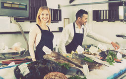 Smiling shop assistants selling fresh fish. And chilled seafood stock photography