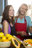 Smiling shop assistants standing at counter with digital tablet stock photos