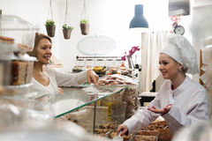 Smiling shop woman offering senior client nuts and smiling. Smiling young shop women offering senior client nuts and smiling royalty free stock photography