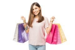 Smiling Shopaholic Woman Carrying Colorful Bags. Over white background stock image