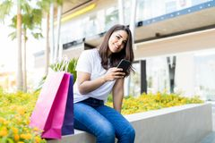 Smiling Shopaholic Woman Social Networking On Mobile Phone Outside Mall royalty free stock photos
