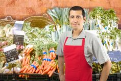 Shopman at the vegetables shop. Smiling shopman at the greengrocer with copyspace Royalty Free Stock Photography