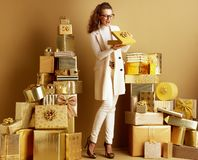 Smiling shopper woman opening golden present box with bow. Full length portrait of smiling stylish shopper woman in white clothes opening golden present box with royalty free stock photo