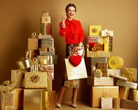 Smiling shopper woman with shopping bag and red heart got idea. Smiling modern shopper woman in red blouse and golden sparkly sequin pencil skirt with shopping stock image