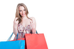 Smiling shopper woman with shopping bags holding finger crossed Royalty Free Stock Images