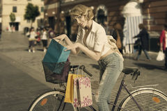 Smiling shopping girl on bicycle vintage color stock photo
