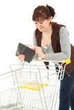 Smiling shopping girl looking to wallet Royalty Free Stock Photography
