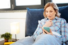 Smiling short-haired mature lady being contented with information. Usual morning routine. Smiling short-haired mature lady being contented with information in royalty free stock photos