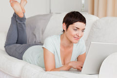 Smiling short-haired woman using a laptop Stock Photography