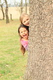 Smiling and shouting girls hiding behind tree royalty free stock photography