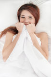 Smiling shy asian woman under a duvet Royalty Free Stock Photography