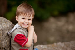 Smiling shy boy. Portrait of happy little shy boy sitting on a stone with blank space on right stock images