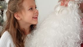Smiling and shy girl sharing her Christmas dreams with Santa. Closeup shot. Professional shot on BMCC RAW with high dynamic range. You can use it e.g. in your Royalty Free Stock Image
