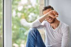 Smiling shy man close face with hand Stock Images