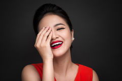 Smiling shy woman closed her face with a hand over black backgro Stock Photo