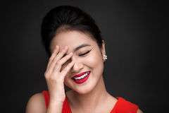 Smiling shy woman closed her face with a hand over black backgro Royalty Free Stock Photos