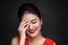 Smiling shy woman closed her face with a hand over black background.  Royalty Free Stock Photo