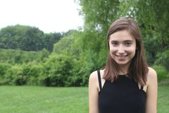 Smiling shy young woman at a big lush park in a black top royalty free stock images