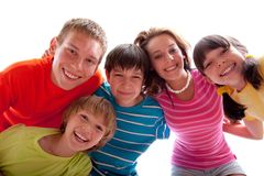 Smiling Siblings. Three brothers and two sisters in casual attire smiling, isolated on a white background Royalty Free Stock Photos