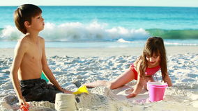 Smiling siblings building sand castles stock footage