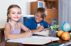 Smiling siblings doing homework with books Stock Photo