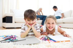 Smiling siblings drawing lying on the floor Royalty Free Stock Photo