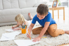 Smiling siblings drawing lying on the floor Stock Photo
