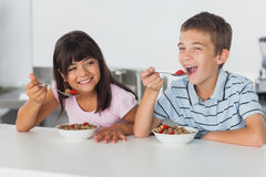 Smiling siblings eating cereal for breakfast in kitchen Royalty Free Stock Photos
