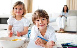 Smiling siblings eating chips and drawing Royalty Free Stock Photos