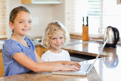Smiling siblings on the laptop in the kitchen Royalty Free Stock Photography