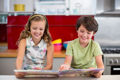 Smiling siblings looking at photo album in kitchen royalty free stock photos