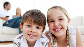 Smiling siblings lying on the floor Stock Images