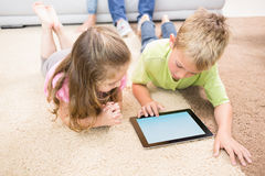 Smiling siblings lying on the rug using a tablet Stock Photo