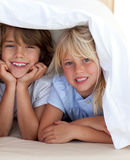 Smiling siblings playing undercover Royalty Free Stock Photos