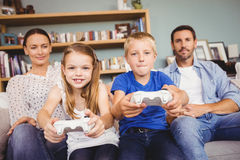 Smiling siblings playing video games with parents Royalty Free Stock Photo
