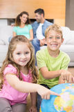 Smiling siblings pointing to globe on the rug Royalty Free Stock Photo