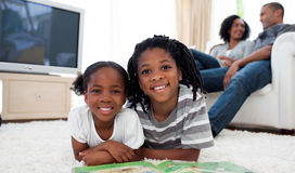 Smiling siblings reading lying on the floor Stock Photo