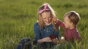 Smiling siblings relaxing on green grass in spring stock video