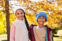 Smiling siblings standing against autumn trees Stock Photos