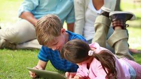 Smiling siblings using an ebook while lying