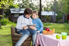 Smiling Siblings Using Tablet Computer At Campsite Stock Photo