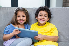 Smiling siblings using tablet on the sofa Stock Images